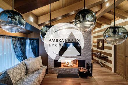 Parete in pietra con televisore e caminetto: Pareti in stile  di Ambra Piccin Architetto