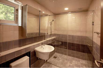 주변 지형과 어우러지는 고급스러운 모던스타일 전원주택[경기 양평]: 지성하우징의  화장실