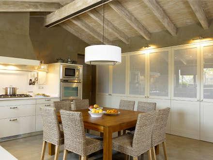 Zona de lavado y planchado oculta en los armarios: Cocinas de estilo rústico de DEULONDER arquitectura domestica