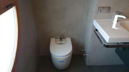 Lavabo suspendido en pared con microcemento: Baños de estilo industrial de Topciment
