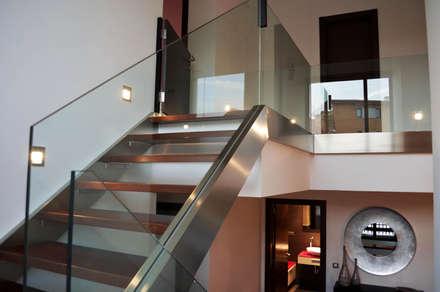 VIVIENDA UNIFAMILIAR EN OLEIROS: Pasillos y vestíbulos de estilo  de Intra Arquitectos