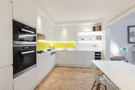 White contemporary kitchen with yellow glass splashbacks and herringbone wood floor: minimalistic Kitchen by Liller Interior