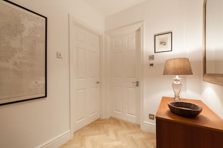 Hallway with eclectic furnishings and herringbone wood floor:  Corridor & hallway by Timothy James Interiors