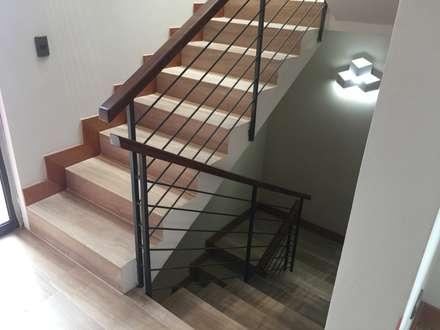 Escalera moldeada con Porcelanato tipo madera: Pasillos, hall y escaleras de estilo  por Arquiespacios