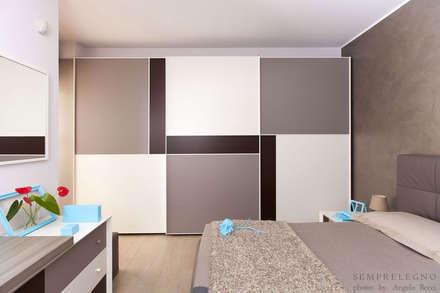 Camera matrimoniale con armadio ad ante scorrevoli su misura: Camera da letto in stile in stile Moderno di Semprelegno