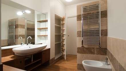 Portaportese - Bagno in travertino: Bagno in stile in stile Moderno di Archifacturing