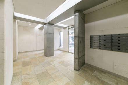エントランスホール:コンクリート打ち放しの柱が空間を彩る: 株式会社YDS建築研究所が手掛けた玄関・廊下・階段です。