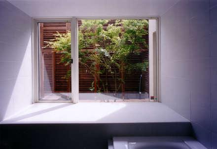 バスルームからパティオを見る: 豊田空間デザイン室 一級建築士事務所が手掛けた浴室です。