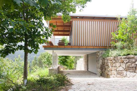 acesso à garagem sob a casa: Habitações  por A+ arquitectura