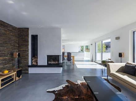 Wohnzimmer mit nach 2 Seiten offenem Kamin: moderne Wohnzimmer von KitzlingerHaus GmbH & Co. KG