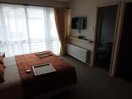 Apart Hotel Madero : Dormitorios de estilo ecléctico por U.R.Q. Arquitectura