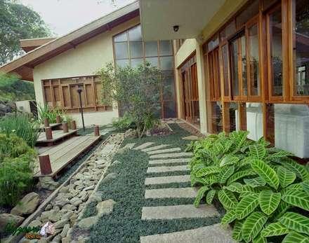 Caminho com pedras no jardim com canaleta de pedra e os seixos de pedras moledo. Casa em condomínio em Atibaia-SP.: Jardins rústicos por Bizzarri Pedras