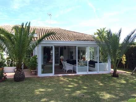 Cerramiento de patio exterior con cortinas de cristal: Casas de estilo clásico de Beldaglass - The In & Out experience