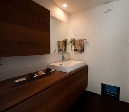 オーダーの洗面化粧 収納力もありながらシンプルなデザインです。: FrameWork設計事務所が手掛けた浴室です。