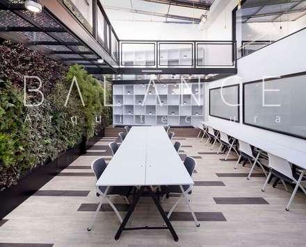 ZONA DE TRABAJO CON MURO VERDE, BIBLIOTECA DOBLE ALTURA Y MOBILIARIO: Espacios comerciales de estilo  por Balance Arquitectura