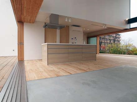 土間とアイランドキッチン: 中庭のある家|水谷嘉信建築設計事務所が手掛けたキッチンです。