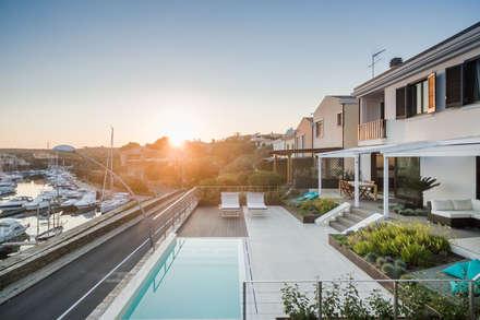 Villa sul Porto: Piscina a sfioro in stile  di Officina29_ARCHITETTI