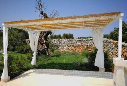 muro a secco sullo sfondo con una vegetazione bassa in modo da poterne apprezzare il restauro: Giardino in stile in stile Mediterraneo di Natura&Architettura