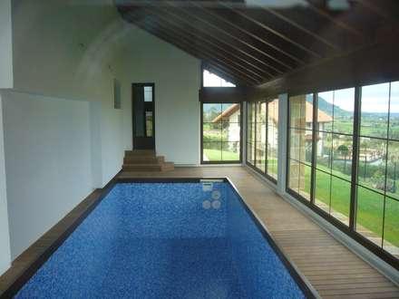 Piscina climatizada: Piscinas de estilo rústico de Arquitecto César Carlón