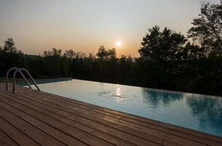 piscina a sfioro e deck in larice: Piscina a sfioro in stile  di de vita e fici architetti associati
