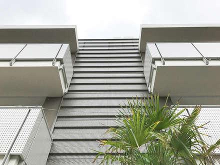 corpo scala/ingresso con rivestimento in lamiera grecata con forature su misura: Scale in stile  di Studio Perini Architetture