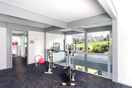 Kundenhaus Friedrichsen - Familienvilla mit Innen-Pool: moderner Fitnessraum von DAVINCI HAUS GmbH & Co. KG