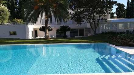 Giardino Privato con piscina: Piscina a sfioro in stile  di STUDIO D'AMICO