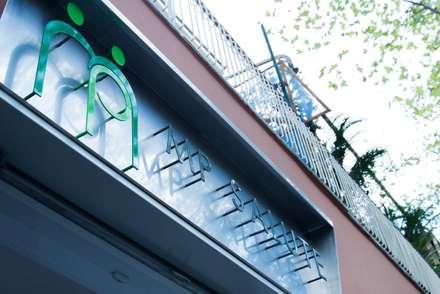 L'insegna retroilluminata, disegnata dallo studio: Ingresso & Corridoio in stile  di VITAE DESIGN STUDIO