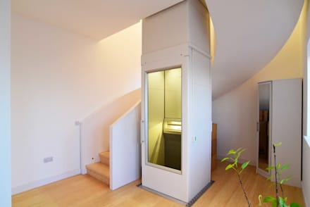 Curved stair in bamboo finish wrapping the lift to the second storey.:  Corridor & hallway by Roundhouse Architecture Ltd