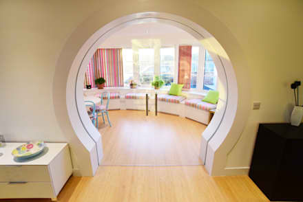 Moongate sliding glass pocket doors leading to the curved dayroom with window seats and blinds continuing the seaside theme.: eclectic Conservatory by Roundhouse Architecture Ltd