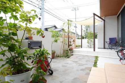 塀の中にも乱形石貼りのデザインが広がる: 株式会社 風知蒼が手掛けた庭です。