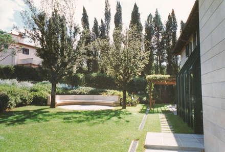 la grande seduta circolare: Giardino anteriore in stile  di Morelli & Ruggeri Architetti