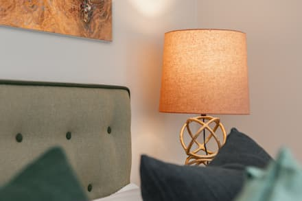 Master bedroom bedside lamp and buttoned headboard: eclectic Bedroom by Timothy James Interiors