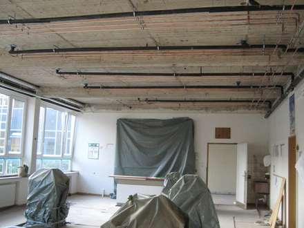 Einbau der Heizrohre unter der Betondecke, die sich später in der runtergehängten Decke befinden sollen.: klassischer Multimedia-Raum von Kaya Architekten