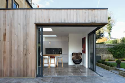Pocket doors open the kitchen out to the garden: minimalistic Houses by Hetreed Ross Architects
