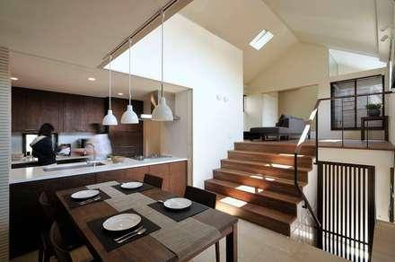 一段上がったリビングと繋がるダイニングキッチン: HAN環境・建築設計事務所が手掛けたリビングです。
