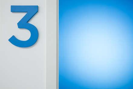 particolare porta e numero sala operatoria: Cliniche in stile  di M2Bstudio