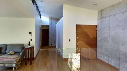 VISTA DESDE LA SALA DE ESTAR A LOS DORMITORIOS: Pasillos y hall de entrada de estilo  por arquiroots