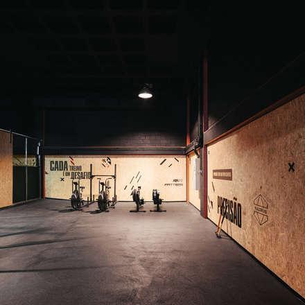 Luminárias suspensas sobre as áreas de treino da crossbox.: Espaços comerciais  por Estúdio AMATAM