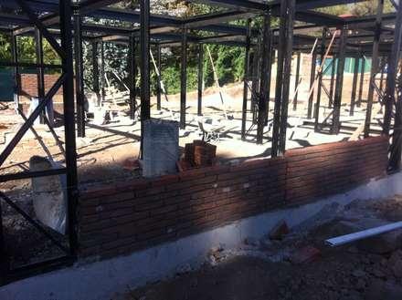 vista de instalación de muros de albañilería entre pilares metálicos: Casas de estilo industrial por MAC SPA