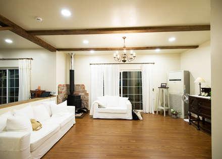 따뜻한 벽난로와 함께하는 거실: (주)메이드의  거실