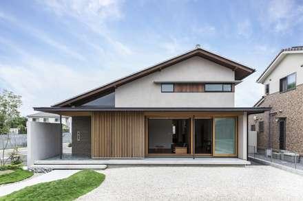 Casas de estilo asiático por WORKS  WISE