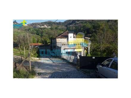 Lateral da casa e entrada garagem (1): Casas de campo  por Clix Mais