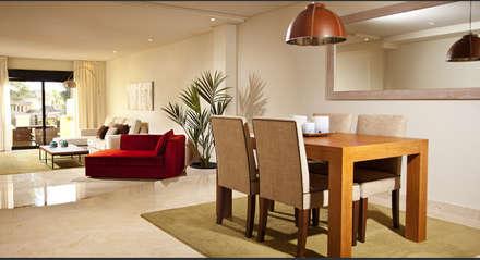 Comedor y salón con mesa de madera y sillas tapizadas de color beige sobre suelo de mármol blanco y sofá rojo que rompe con los colores claros: Comedores de estilo tropical de AVANTUM
