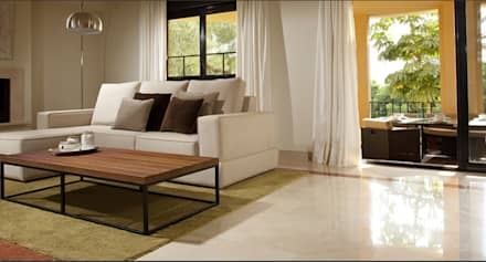 Salón con sofá en forma de L blanco y mesa de madera y hierro forjado sobre alfombra verde: Comedores de estilo tropical de AVANTUM