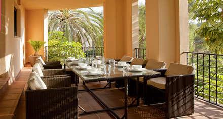 Terraza decorada con un juego de mesa y sillas de mimbre: Comedores de estilo tropical de AVANTUM