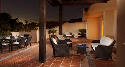 Terraza de baldosas naranjas  con zona chill out con juego de mesa de mimbre y cristal y sillas de mimbre y cojín blanco: Terrazas de estilo  de AVANTUM