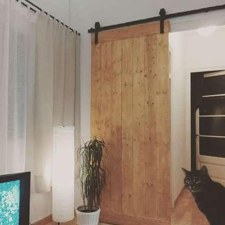 Puerta madera rústica con guia industrial de hierro: Comedores de estilo industrial de Casolart