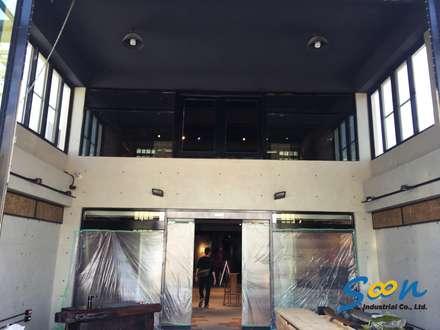 一樓特別作了挑高約 4.5 米的設計,下方兩側保有滿滿的展示架空間,而上方則安裝了 1 米 5 高的橫拉窗,豪邁的引入高雄熱情陽光,同時也能做大面積的通風。:  辦公室&店面 by Soon Industrial Co., Ltd.