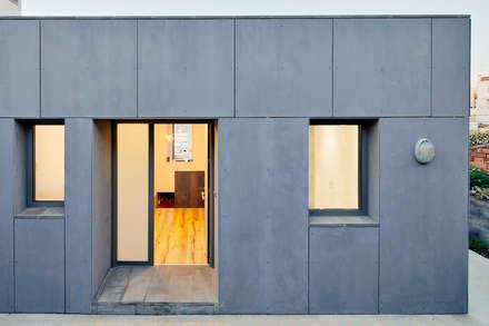 Marian. Casa sobre el muro: Casas unifamilares de estilo  de miliunarquitectura